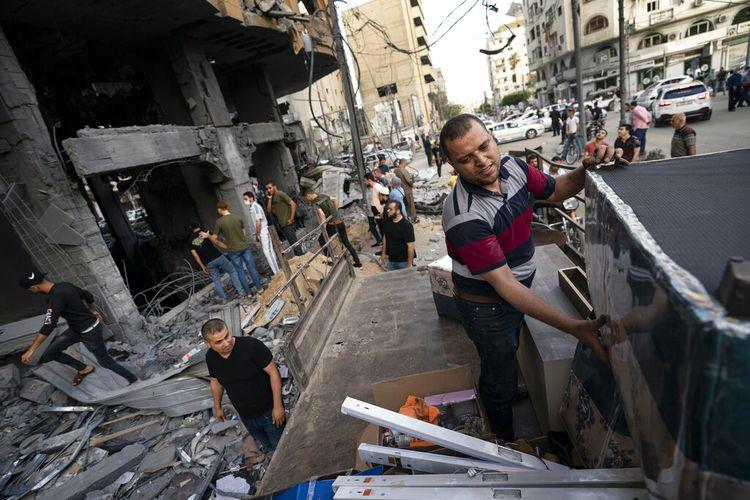 Orang-orang menyelamatkan barang-barang berharga dari dalam gedung Al-Jawhara yang rusak parah menyusul gencatan senjata yang dicapai setelah perang 11 hari antara penguasa Hamas Gaza dan Israel, di Kota Gaza, Jumat, 21 Mei 2021.