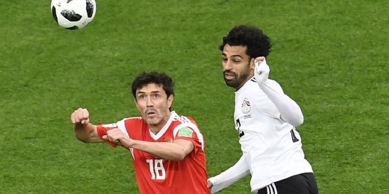 Yuri Zhirkov dan Mohamed Salah mencoba menyundul bola pada pertandingan Rusia vs Mesir di St. Petersburg, 19 Juni 2018.