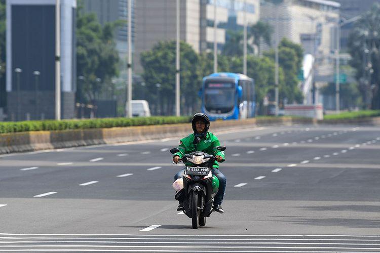 Pengendara ojek daring melintasi jalan MH Thamrin, Jakarta, Minggu (29/3/2020). Pemprov DKI Jakarta melakukan pembatasan aktivitas di Ibu Kota dengan memperpanjang masa tanggap darurat COVID-19 hingga 19 April 2020 sehubungan dengan meluasnya pandemi COVID-19.
