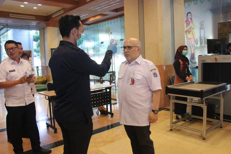 Asisten Pemerintahan Sekda DKI Jakarta Artal Reswan Soewardjo saat diperiksa suhu tubuhnya di Balai Kota dalam rangka antisipasi Virus Corona, Rabu (4/3/2020)