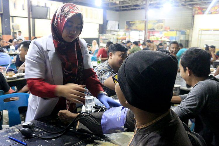 Petugas dari Palang Merah Indonesia (PMI) Kota Banda Aceh sedang menawarkan kesediaan pendonor darah yang sedang nongkrong di warung kopi yang berada kawasan Darussalam , Kota Banda Aceh, Sabtu 925/05/2019).