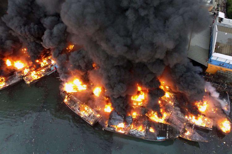 Asap tebal mengepul dari kapal-kapal yang terbakar di Pelabuhan Muara Baru, Jakarta Utara, Sabtu (23/2/2019). Hingga pukul 18.30 api masih terlihat membakar beberapa kapal, meski begitu proses pemadaman masih di lakukan,  di tengah angin yang kencang.