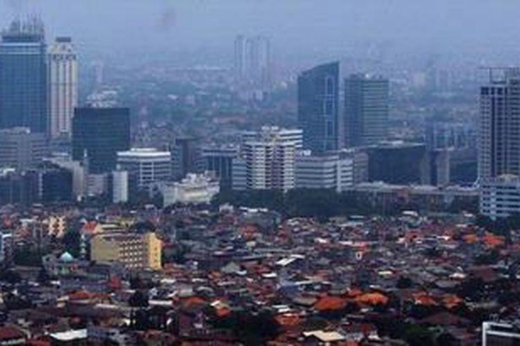 Kepadatan permukiman penduduk berlatar belakang gedung bertingkat terlihat dari ketinggian di Jakarta, Senin (12/12/2011).