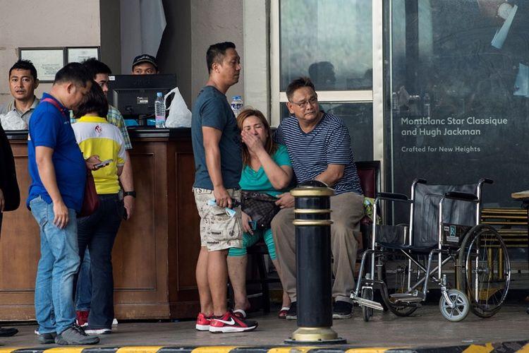 Para keluarga korban serangan kasino duduk di depan hotel World Resort Manila menunggu kabar nasib kerabat mereka.