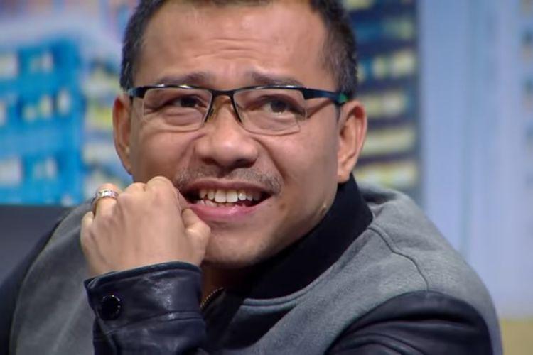 Senyum masam Anang Hermansyah mendengar seorang kontestan Indonesian Idol X bernyanyi.