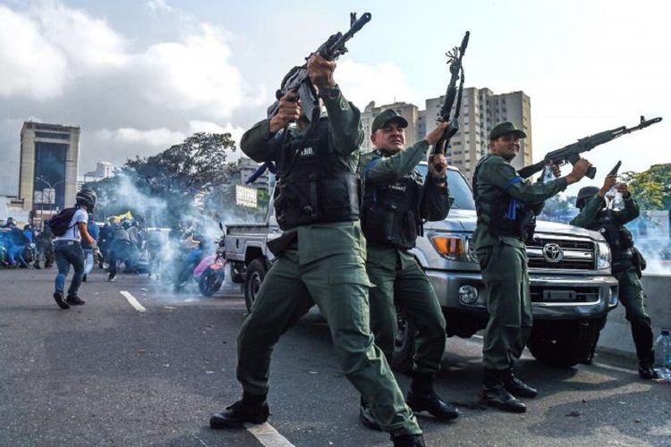 Anggota dari Garda Nasional Bolivarian yang memilih mendukung oposisi Venezuela pimpinan Juan Guaido membalas tembakan pasukan loyalis Presiden Nicolas Maduro dalam ketegangan yang terjadi  di Caracas, Selasa (30/4/2019).