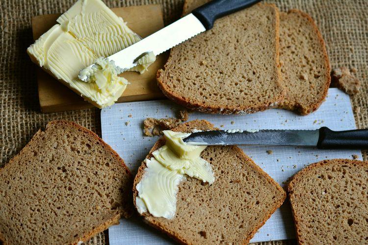 Ilustrasi roti tawar buatan sendiri yang dinikmati dengan olesan mentega.