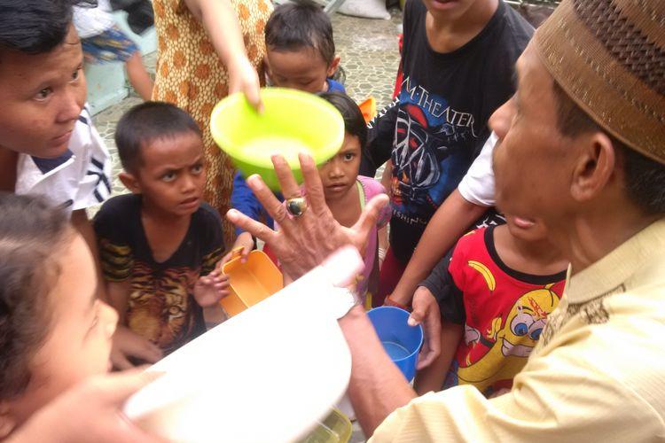 Warga disekitar masjid Suro mengantre untuk meminta bubur suro yang hanya dibuat saat bulan suci ramadhan di Palembang, Sumatera Selatan
