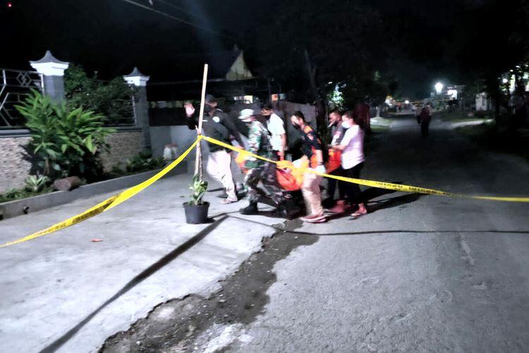 Petugas mengevakuasi jasad AM, korban penganiayaan hingga tewas, dari lokasi kejadian di Kelurahan Babadan, Kecamatan Wlingi, Kabupaten Blitar, Selasa tengah malam (21/9/2021)