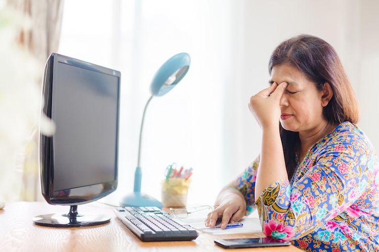 Seseorang yang mengalami zoom fatigue akibat bekerja lama di depan laptop