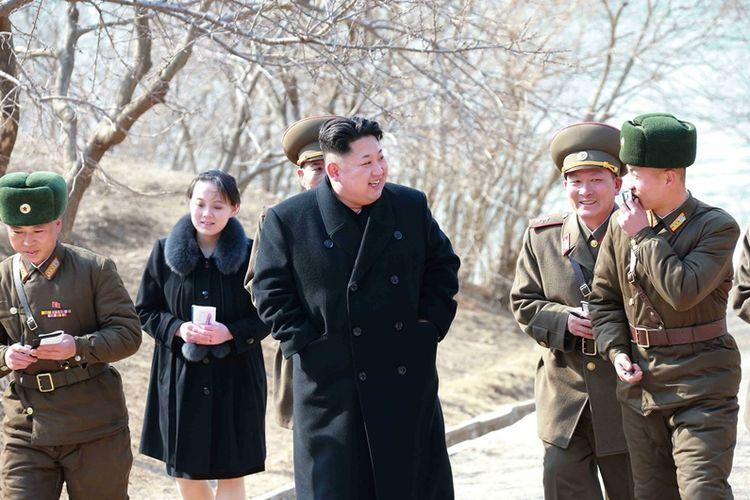 Foto bertanggal 12 Maret 2015 memperlihatkan adik Kim Jong Un, Kom Yo Jong (belakang, bermantel hitam) tengah mendampingi sang kakak meninjau perusahaan senjata, Sin Islet, di Provinsi Kangwon.