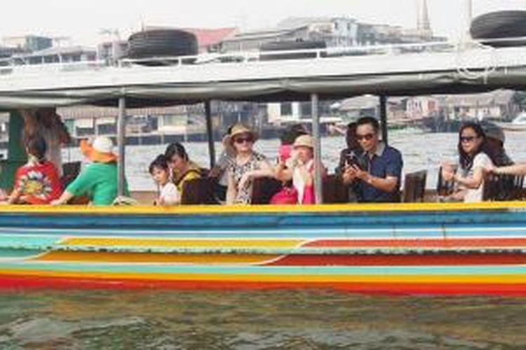 Wisatawan asing memberi makan ikan Patin di Sungai Chaophraya, Bangkok, Thailand.