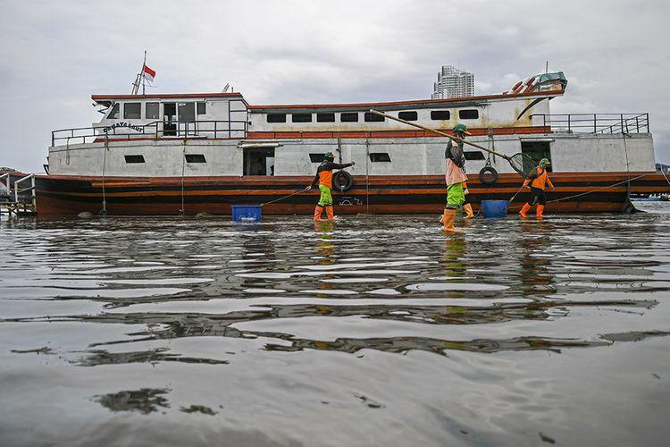 Petugas kebersihan beraktivitas saat banjir rob di Pelabuhan Kali Adem, Muara Angke, Jakarta, Jumat (1/1/2021). Banjir yang terjadi sejak Kamis (31/12/2020) itu dikarenakan pasang surut air laut.