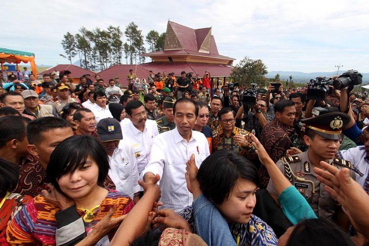 Presiden Joko Widodo menyapa warga saat tiba di kawasan perumahan relokasi pengungsi Gunung Sinabung di Desa Siosar, Karo, Sumatera Utara, Sabtu (14/10). Perumahan untuk relokasi pengungsi Sinabung yang dipersiapkan sebanyak 370 rumah baru itu akhirnya selesai dan telah dihuni oleh para pengungsi.