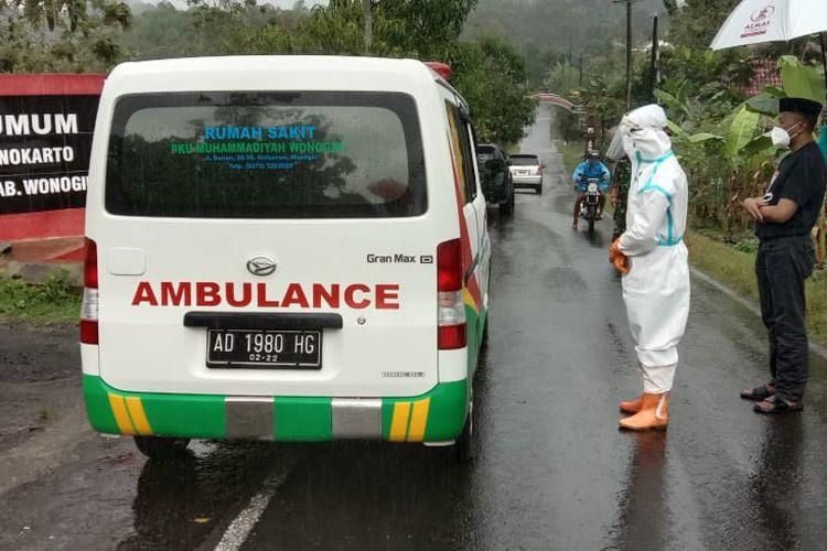 SOLATKAN—Sebelum dimakamkan, satu anggota tim menyolatkan jenazah pasien covid-19 yang berada didalam mobil ambulan.