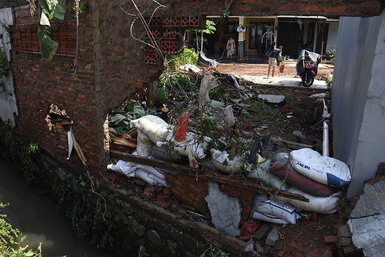 Warga membersihkan rumahnya pascabanjir yang merobohkan tembok pembatas kali di perumahan Green Malaka Residence, Ciracas, Jakarta, Minggu (11/10/2020). Banjir yang merendam sejumlah permukiman di Ciracas itu disebabkan karena meluapnya Kali Cipinang akibat hujan lebat pada Sabtu (10/10) kemarin