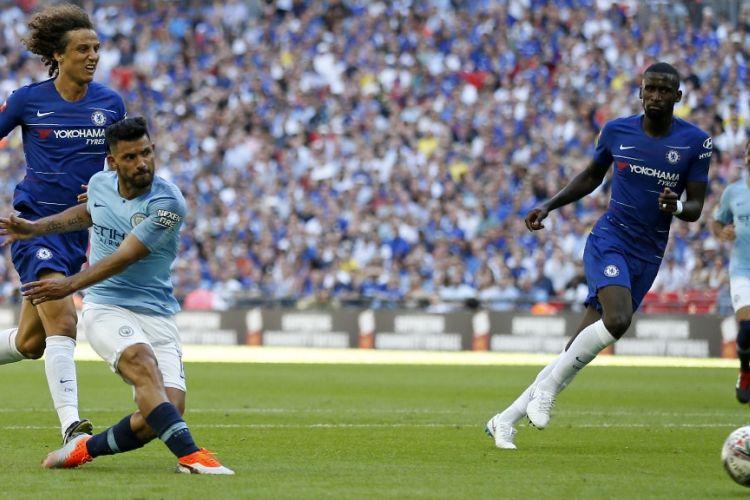 Striker Manchester City, Sergio Aguero, melepaskan tembakan yang berujung gol ke gawang Chelsea pada pertandingan Community Shield di Stadion Wembley, London, Minggu (5/8/2018).
