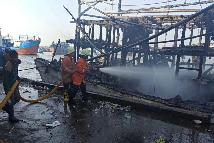 Petugas memadamkan api kapal nelayan yang terbakar di Pelabuhan Muara Baru, Jakarta Utara, Rabu (28/7/2021).