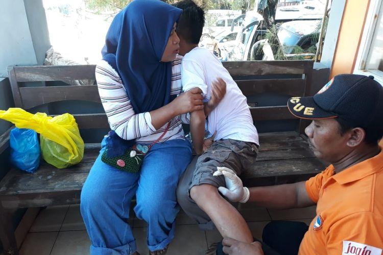 Petugas SAR Satlinmas Wilayah II Gunungkidul Membantu Wisatawan yang Tersengat Ubur-ubur di Pos SAR Pantai Sepanjang Kamis (6/6/2019).