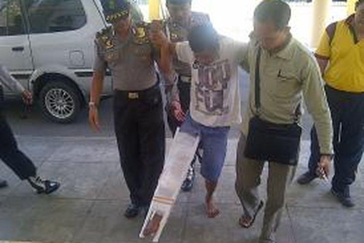 Pelaku utama perampokan dan pembunuhan terhadap dua balita, Ahmad Musa (28) usai dibawa dari rumah sakit akibat ditembak di bagian kaki kanan saat dilakukan penangkapan, Jumat (11/10/2013)