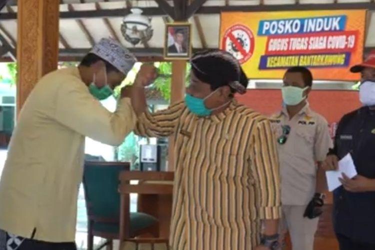 Kepala Dinas Kesehatan Kabupaten Brebes dr. Sartono melakukan salam siku dengan Romli saat mengantar kepulangannya ke Kantor Kecamatan Bantarkawung, Brebes, Kamis (25/6/2020) (Foto: Dok. Dinas Kesehatan Brebes)