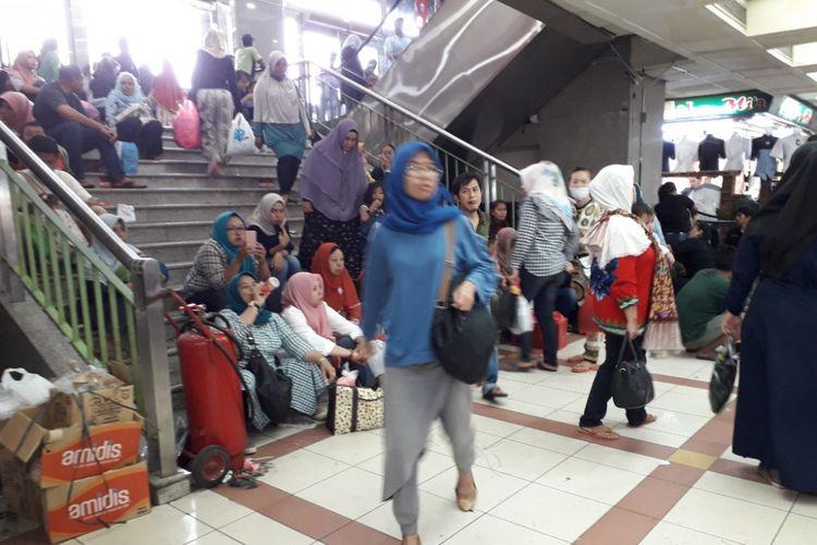 Pengunjung Pasar Tanah Abang terpaksa duduk di anak tangga akibat sedikitnya jumlah bangku di pusat grosir terbesar se-Asia Tenggara tersebut, Sabtu (12/5/2018).