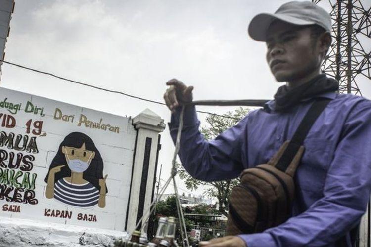 Pedagang yang tidak mengenakan masker berjalan di depan mural yang berisi pesan waspada virus Corona di Petamburan, Jakarta, Rabu (16/09)