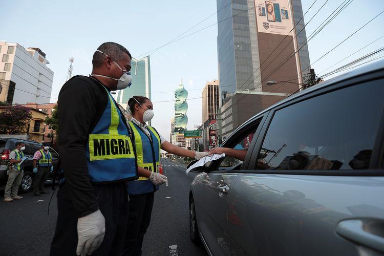 Kepolisian mengecek dokumen dari sopir selama penerapan lockdown mencegah virus corona di Panama City, Panama, pada 31 Maret 2020.
