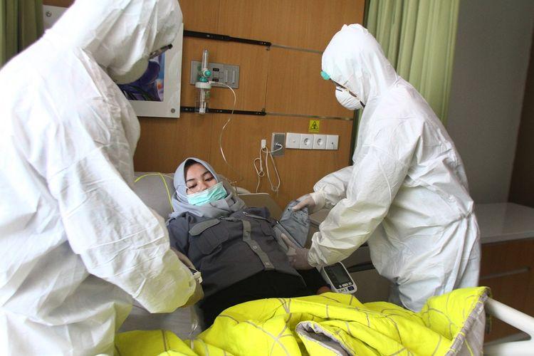 Petugas medis memeriksa kondisi pasien di ruang isolasi saat simulasi Penanganan Pasien Corona di Rumah Sakit Lavalette, Malang, Jawa Timur, Jumat (13/3/2020). Simulasi tersebut untuk memastikan kesiapan sarana ruang isolasi dan peralatan medis sekaligus melatih koordinasi dalam penanganan pasien Covid-19 termasuk diantaranya penggunaan kostum Alat Pelindung Diri (APD). ANTARA FOTO/Ari Bowo Sucipto/ama.