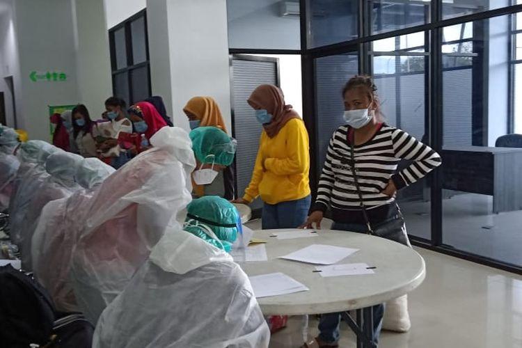 Petugas medis sedang mengukur suhu tubuh dan melakukan rapid tes bagi WNI yang dideportasi dari Tawau, Malaysia menuju Pelabuhan Tunon Taka, Nunukan, Kaltara, Rabu (3/6/2020).