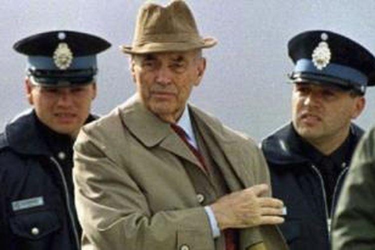 Mantan kapten pasukan SS Nazi, Erich Priebke, digiring polisi Argentina menuju pesawat terbang yang akan membawanya ke Italia pada 1995. Setelah diadili di Roma, pada 1998, Priebke dijatuhi hukuman seumur hidup setelah terbukti membantai 335 orang warga sipil Italia pada Maret 1944.