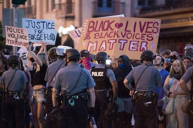 Dalam foto 29 Mei 2020 ini, polisi dengan alat pelindung menahan para pengunjuk rasa selama protes atas kematian George Floyd di Country Club Plaza di Kansas City.