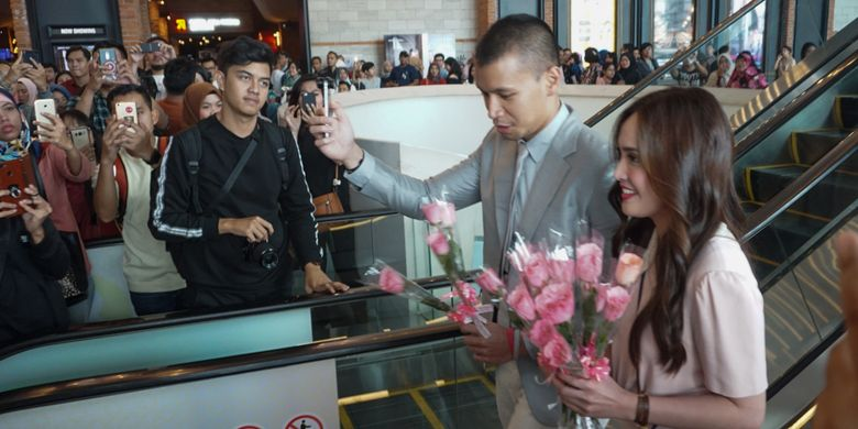 Artis peran Shandy Aulia dan Samuel Rizal saat membagikan bunga pada penggemar di pemutaran khusus film Eiffel Im In Love 2 di CGV Grand Indonesia, Tanah Abang, Jakarta Pusat, Minggu (11/2/2018).