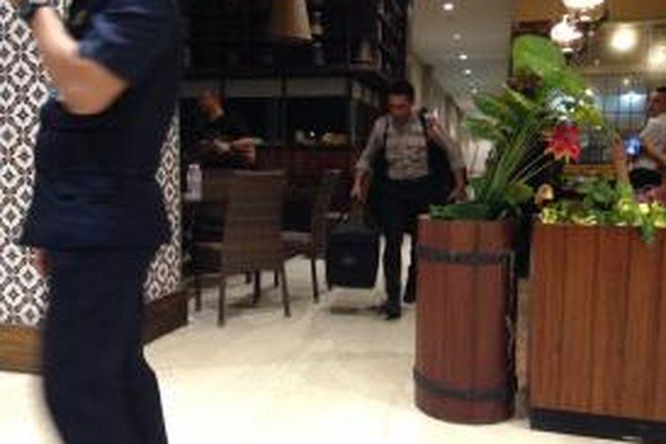 Personel polisi membawa sebuah tas hitam keluar dari tempat terjadinya ledakan di toilet pria Mal Alam Sutera, Tangerang, Kamis (9/7/2015) malam. Ledakan diduga akibat bom yang terjadi pada Kamis siang.