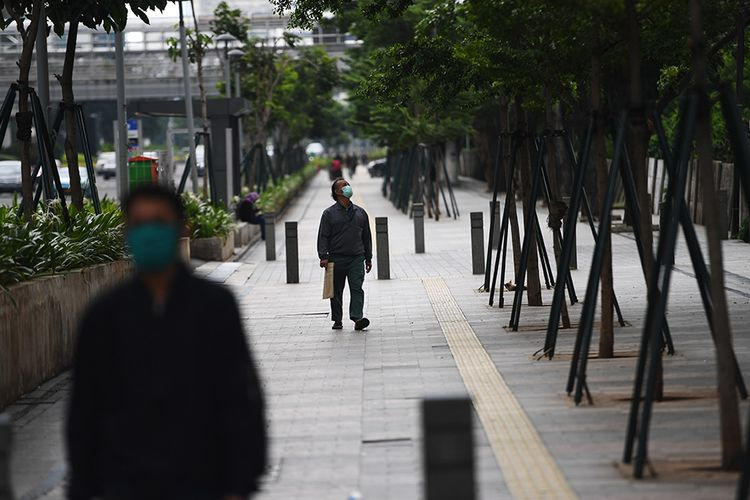Pejalan kaki melintas di trotoar Jalan Jenderal Sudirman, Jakarta, Selasa (7/4/2020). Pemerintah telah resmi menetapkan Pembatasan Sosial Berskala Besar (PSBB) di wilayah DKI Jakarta dalam rangka percepatan penanganan COVID-19.