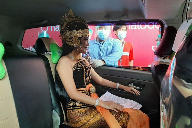 Tokoh Shinta saat divaksinasi dari dalam mobil. Vaksinasi massal dengan metode drive thru ini untuk para pelaku pariwisata dan pekerja transportasi umum. Kegiatan ini dilaksanakan di taman Parkir Ramayana Ballet, kompleks Candi Prambanan.