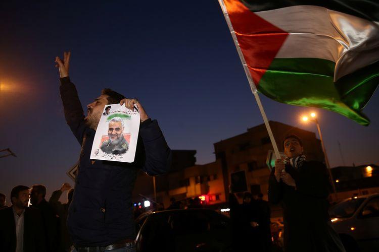 Seorang pria memegang gambar mendiang Komandan Pasukan Quds, Mayor Jenderal Qasem Soleimani, di tengah perayaan setelah Iran melancarkan serangan rudal terhadap pangkalan AS di Irak pada 8 Januari 2020.