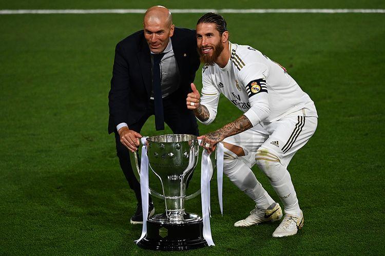 Pelatih Real Madrid Zinedine Zidane (kiri) dan bek Real Madrid Sergio Ramos berpose dengan trofi usai timnya berhasil menjadi juara Liga Spanyol setelah mengalahkan Villarreal 2-1 di Stadion Alfredo di Stefano, Valdebebas, pada Jumat (17/7/2020) dini hari WIB. Hasil ini menjadi trofi Liga Spanyol ke-34 Real Madrid dan yang ke-11 bagi Zinedine Zidane menangani Los Blancos, termasuk tiga gelar Liga Spanyol.