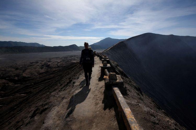 Wisatawan melintas di bibir kaldera Gunung Bromo, Probolinggo, Jawa Timur, Sabtu (4/11/2017). Pada hari libur kawasan wisata Gunung Bromo ramai dikunjungi wisatawan domestik dan manca negara.
