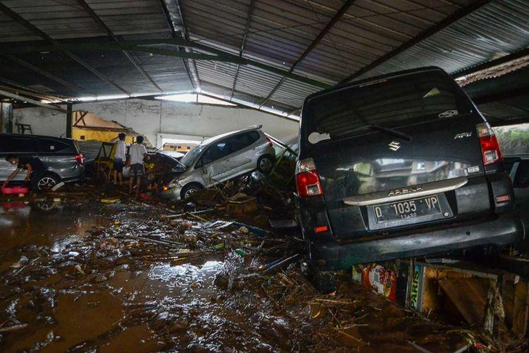 Warga mengamati kendaraan yang terseret banjir bandang di Cicaheum, Bandung, Jawa Barat, Selasa (20/3/2018). Banjir bandang yang disertai lumpur tersebut disebabkan oleh luapan Sungai Cipamokolan akibat intensitas hujan yang tinggi di beberapa wilayah Kota Bandung.