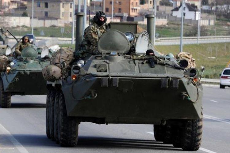 Iring-iringan kendaraan lapis baja Rusia bergerak di jalan raya yang menghubungkan ibu kota Crimea, Simferopol dengan kota pelabuhan, Sevastopol.