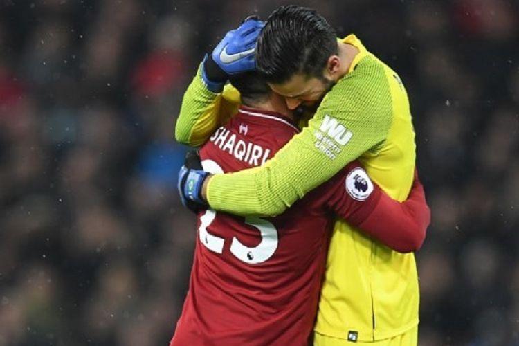 Alisson Becker dan Xherdan Shaqiri berpelukan seusai laga Liverpool vs Manchester United dalam pertandingan pekan ke-17 Liga Inggris di Stadion Anfield, 16 Desember 2018.