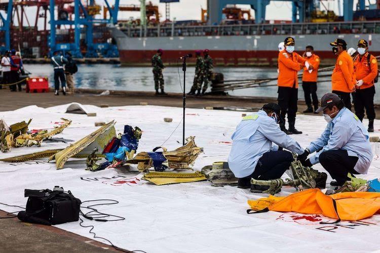 Anggota Komite Nasional Keselamatan Transportasi (KNKT) memeriksa bagian pesawat Sriwijaya Air SJ 182 rute Jakarta - Pontianak yang jatuh di perairan Pulau Seribu di Dermaga JICT 2, Tanjung Priok, Jakarta Utara, Minggu (10/1/2021). Temuan bagian pesawat selanjutnya akan diperiksa oleh KNKT sedangkan potongan tubuh korban diserahkan kepada DVI Polri untuk identifikasi lebih lanjut.(KOMPAS.com/GARRY LOTULUNG)