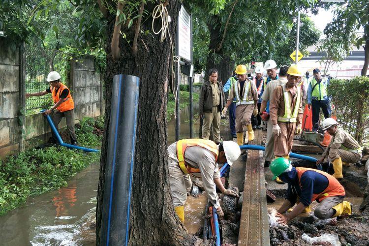 Petugas PT Palyja memperbaiki pipa yang pecah di Jalan Terusan HR Rasuna Said, Selasa (20/2/2018). Akibat pipa pecah, air menggenangi jalan tersebut.