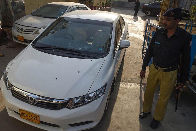 Polisi Pakistan berjaga di samping mobil yang ditumpangi warga China korban penembakan di Karachi, Senin (5/2/2018).