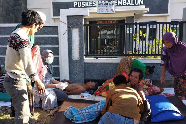 Warga korban gempa mendapatkan perawatan di luar Puskesmas Sembalun Selong, Lombok Timur, NTB, Minggu (29/7/2018). Berdasarkan informasi dari Badan Meteorologi Klimatologi dan Geofisika (BMKG) gempa pertama kali mengguncang Lombok Timur dengan kekuatan 6,4 skala Richter (SR) pada pukul 06.47 Wita.