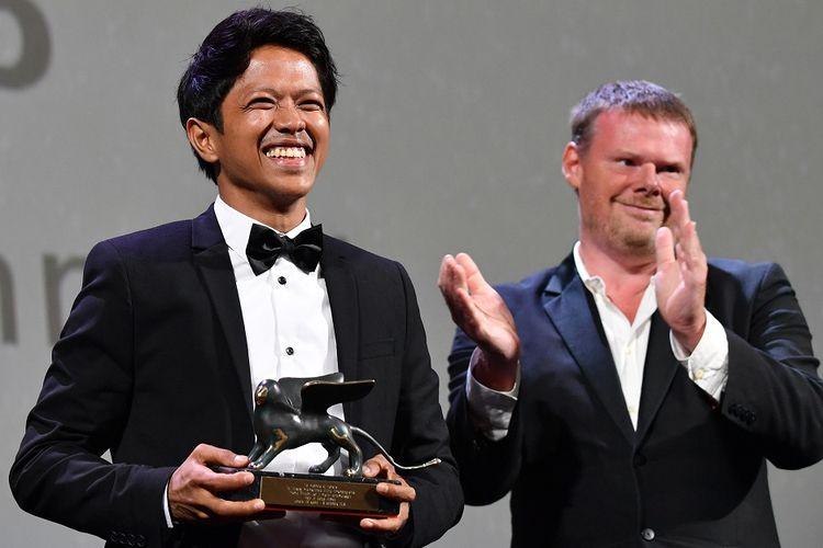 Sutradara asal Indonesia Aditya Ahmad (kiri) menggenggam trofi Best Short Film untuk film Kado dalam Orizzonti Awards pada The 75th Venice International Film Festival, Italia, Sabtu (8/9/2018) waktu setempat.