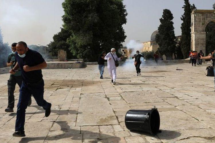 Polisi Israel melempar granat ke arah orang Palestina yang membalas dengan lembaran batu dan benda lain dalam bentrokan di seputar Masjid Al-Aqsa di kawasan Yerusalem Timur yang diduduki Senin (10/5/2021).