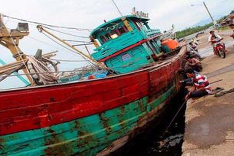 Warga memancing ikan di tepi kapal nelayan yang bersandar di pelabuhan perikanan Pulau Baai, Kota Bengkulu, Provinsi Bengkulu, Selasa (8/1/2012). Sebagian kecil nelayan di Pulau Baai tidak berani melaut dan menyandarkan kapalnya di pelabuhan karena buruknya cuaca. Namun, mayoritas dari mereka tetap memaksakan diri melaut.