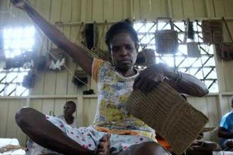 Warga menyelesaikan pembuatan noken (tas dari Papua) dari tali sagu di Sanggar Kelompok Gescu Cepes, Kampung Jasiw, Distrik Atsy, Kabupaten Asmat, Papua, Minggu (18/8/2013). Hasil kerajinan anyaman khas Asmat itu dijual Rp 500.000 per tas.